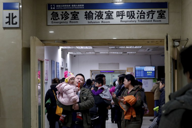Parents with their children wait at a holding room of a children hospital in Beijing, Sunday, Dec. 18, 2016. A smog-shrouded Chinese city canceled airline flights Sunday due to poor visibility and many parents took children to hospitals on the second day of a pollution alert across the country's north. (AP Photo/Andy Wong)