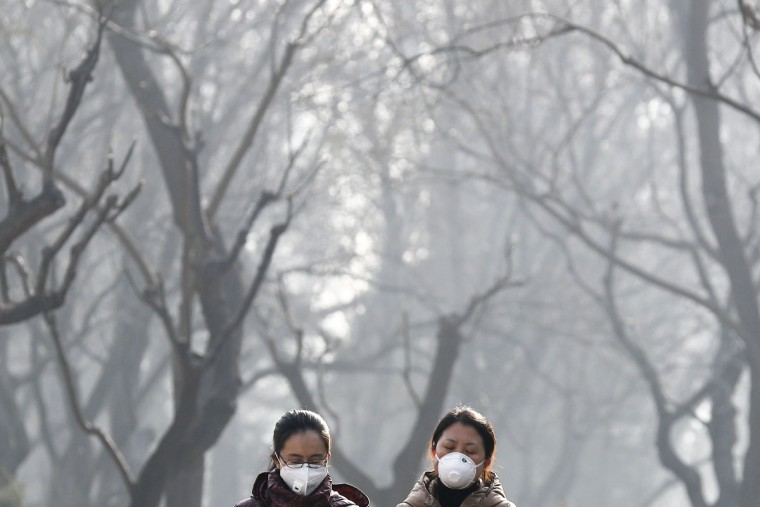 "Chinese women wearing masks for protection against air pollution walk through Ritan Park shrouded by dense smog in Beijing, Monday, Dec. 19, 2016. Chinese cities are limiting the number of cars on roads and have temporarily shut down factories to cut down pollution during a national ""red alert"" for smog. (AP Photo/Andy Wong)"