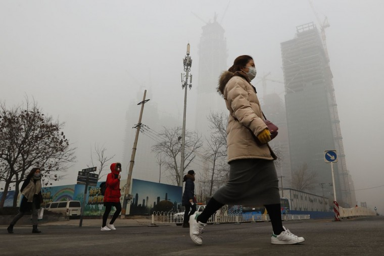 Women wearing protection masks walk across a road in Beijing as the capital of China is shrouded by heavy smog on Tuesday, Dec. 20, 2016. Thick, gray smog fell over Beijing on Tuesday, clouding China's capital in a haze that spurred authorities to cancel flights and close some highways in emergency measures to cut down on air pollution. (AP Photo/Andy Wong)