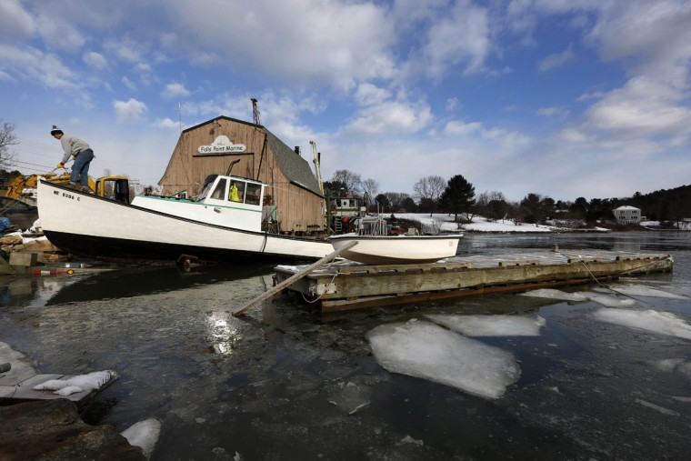 Lobsterman Jack O'Donoghue checks his bow line while getting his 30-foot fishing boat, Mary Elizabeth, hauled out of the icy Harraseeket River in advance of winter Thursday, Dec. 15, 2016, in Freeport, Maine. (AP Photo/Robert F. Bukaty)