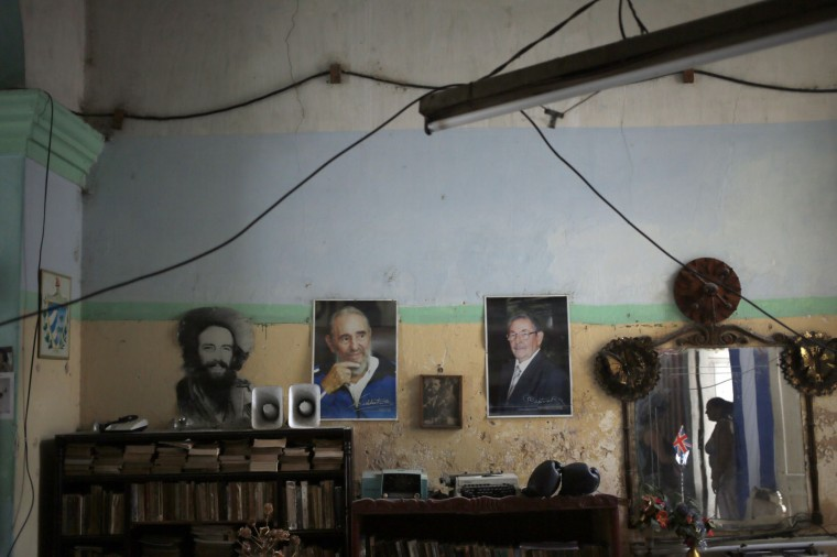 In this Dec. 1, 2016 photo, Elisa Ricardo, reflected in the mirror at right, stands in her living room decorated with images of Cuba's President Raul Castro, right, his late brother Fidel Castro, center, and late revolutionary hero Camilo Cienfuegos, left, in Old Havana, Cuba. President Raul Castro said the country would bar statues of Fidel Castro and monuments bearing his name in keeping with the former leader's desire to prevent the growth of a cult of personality. (AP Photo/Enric Marti)