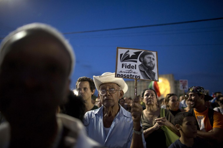 "In this Nov. 29, 2016 photo, a man holds a sign with a picture of Fidel Castro that reads in Spanish ""Fidel among us'"" during a rally honoring the late Cuban leader at Revolution Plaza in Havana, Cuba. Schools and government offices were closed in homage to Fidel Castro, with the day ending in a rally on the wide plaza where the Cuban leader delivered fiery speeches to mammoth crowds in the years after he seized power. (AP Photo/Natacha Pisarenko)"
