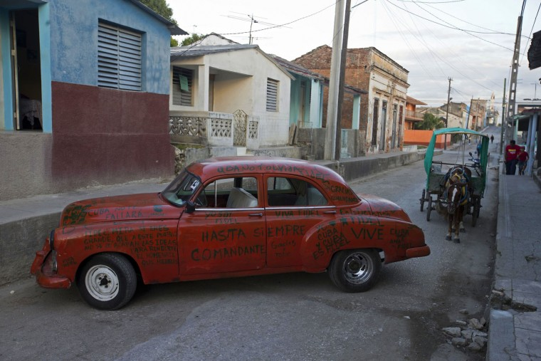 In this Nov. 30, 2016 photo, a car covered with messages to Cuba's leader Fidel Castro is parked in La Esperanza, Cuba. Castro's ashes journeyed in a funeral procession that retraced the path of his triumphant march into Havana nearly six decades ago in a four-day journey across Cuba from the capital to their final resting place in the eastern city of Santiago. President Raul Castro said Cuba would bars statues of Castro and monuments bearing his name in keeping with the former leader's desire to prevent the growth of a cult of personality. (AP Photo/Ricardo Mazalan)