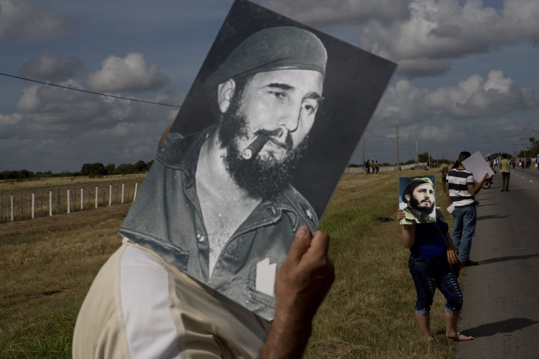 In this Dec. 2, 2016 photo, a man uses a picture of Fidel Castro to shade himself from the sun while waiting for the convoy carrying the ashes of Cuba's late leader, along the central road near Yarigua, Las Tunas, Cuba. Castro's ashes journeyed across Cuba from Havana to their final resting place in the eastern city of Santiago. (AP Photo/Rodrigo Abd)