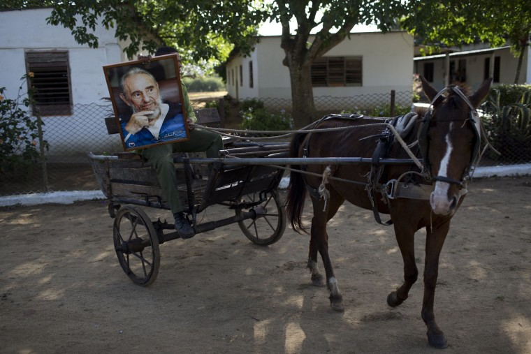 In this Nov. 30, 2016 photo, Michael Mendoza carries a portrait of the late Cuban leader Fidel Castro, in his horse-drawn taxi carriage in Camaguey, Cuba. Castro's ashes retraced the journey he made from Santiago to Havana, passing trough Camaguey, after his rebel force won power in 1959, in a solemn procession to his final resting spot. (AP Photo/Rodrigo Abd)