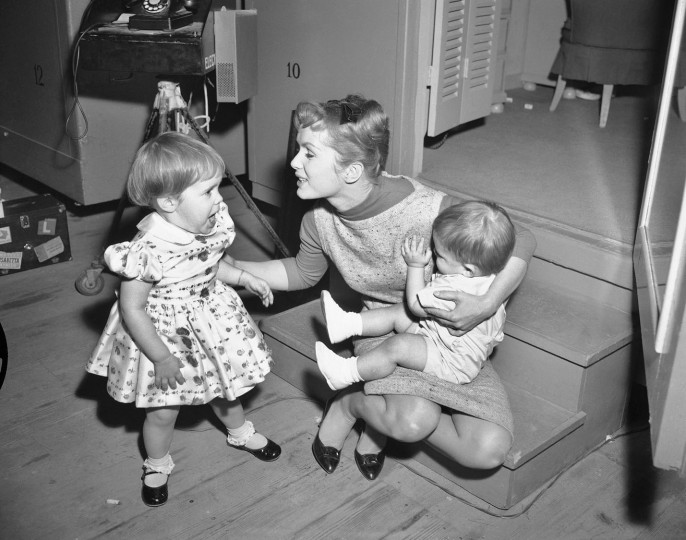 "FILE- In this Feb. 27, 1959, file photo, working long hours on the set of ""Say One For Me,"" so she can fly to Spain and start another movie, actress Debbie Reynolds is visited at the studio by her children, Carrie, 2, and 1-year-old Todd. Reynolds, star of the 1952 classic ""Singin' in the Rain"" died Wednesday, Dec. 28, 2016, according to her son Todd Fisher. She was 84. (AP Photo, File)"