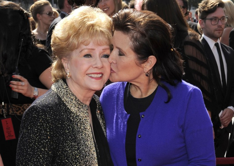 "FILE- In this Sept. 10, 2011, file photo, Debbie Reynolds, left, and Carrie Fisher arrive at the Primetime Creative Arts Emmy Awards in Los Angeles. Reynolds, star of the 1952 classic ""Singin' in the Rain"" died Wednesday, Dec. 28, 2016, according to her son Todd Fisher. She was 84. (AP Photo/Chris Pizzello, File)"