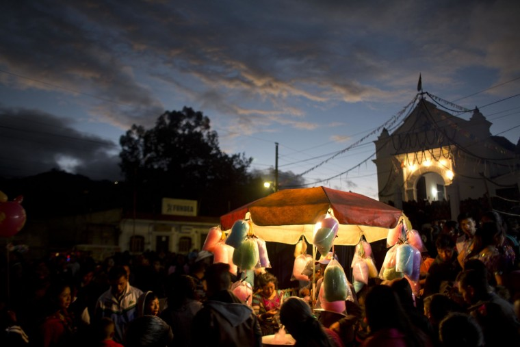 People buy cotton candy outside El Calvario church during celebrations honoring Saint Thomas, the patron saint of Chichicastenango, Guatemala, Wednesday, Dec. 21, 2016. The church is built atop a former temple and incorporates the temple's 18 steps, each representing a month of the Mayan calendar. (AP Photo/Moises Castillo)