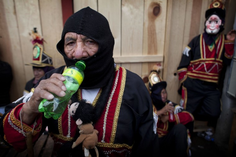 A dancer drinks water as he rests during celebrations honoring Saint Thomas, the patron saint of Chichicastenango, Guatemala, Wednesday, Dec. 21, 2016. The Feast of Saint Thomas draws international tourists with its colorful pageantry, but at its heart is a religious celebration melding Catholic and indigenous traditions that culminates on Dec. 21. (AP Photo/Moises Castillo)