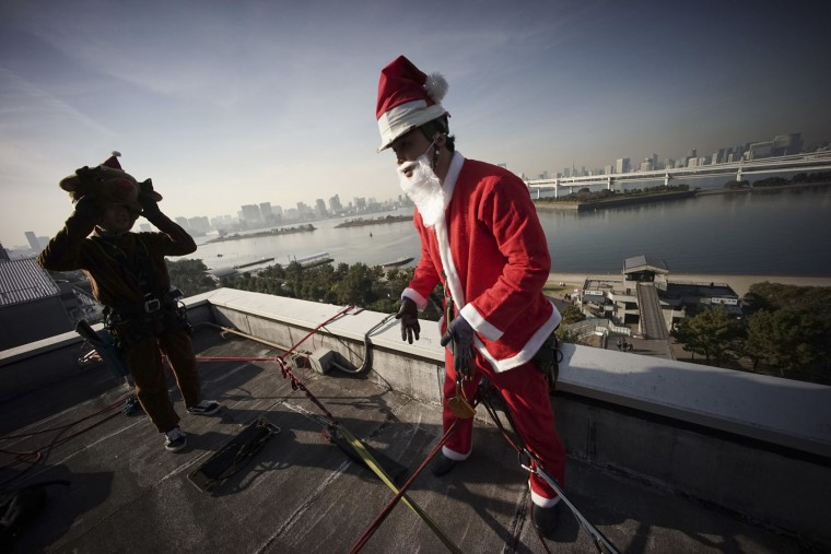 Window cleaners dressed as Santa Claus and reindeer prepare cleaning windows at a shopping mall in Tokyo's Daiba bay area, Wednesday, Dec. 21, 2016. (AP Photo/Eugene Hoshiko)