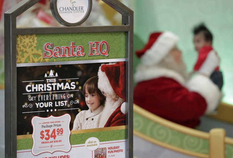 In this Thursday, Nov. 17, 2016, photo, a child has his photo taken with Santa Roger Edmonds at the Santa HQ at the Chandler Mall, in Chandler, Ariz. (AP Photo/Matt York)