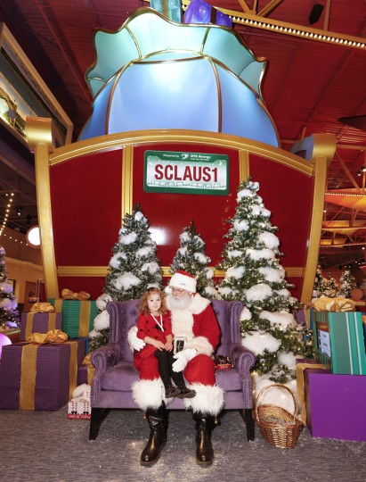 In this Monday, Nov. 21, 2016, photo, Sophie Golding, 3, sits on Santa's lap for a photograph at Santa's Flight Academy in Great Lakes Crossing Outlets in Auburn Hills, Mich. In addition to having Santa, many malls are installing shows and games they hope will lure shoppers who are buying more online. (AP Photo/Paul Sancya)