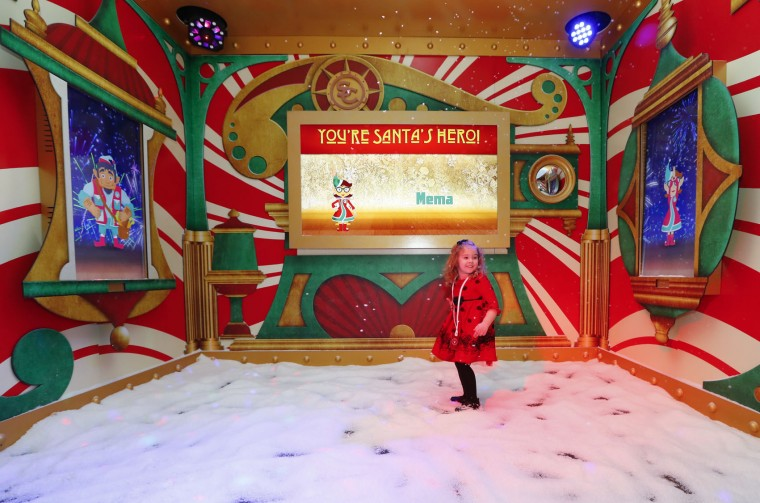 In this Monday, Nov. 21, 2016, photo, Sophie Golding, 3, plays at Santa's Flight Academy in Great Lakes Crossing Outlets in Auburn Hills, Mich. In an effort to lure online shoppers to their stores, many malls are upgrading the traditional visit to Santa into a high-tech experience. (AP Photo/Paul Sancya)