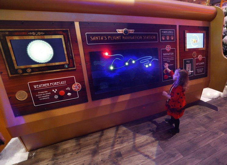 In this Monday, Nov. 21, 2016, photo, Sophie Golding, 3, checks Santa's route at Santa's Flight Academy in Great Lakes Crossing Outlets in Auburn Hills, Mich. In an effort to lure online shoppers to their stores, many malls are upgrading the traditional visit to Santa into a high-tech experience. (AP Photo/Paul Sancya)