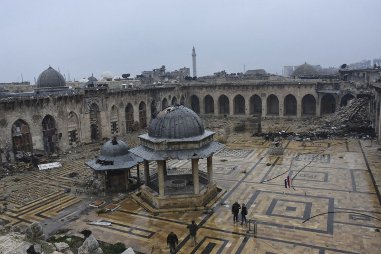 This photo released by the Syrian official news agency SANA, shows Syrian troops and pro-government gunmen marching walk inside the destroyed Grand Umayyad mosque in the old city of Aleppo, Syria, Tuesday, Dec. 13, 2016. Government forces and rebel fighters have fought to control the 12th century mosque in the last four years, until Syrian troops seized control of it this week. Syrian rebels said Tuesday that they reached a cease-fire deal with Moscow to evacuate civilians and fighters from eastern Aleppo, after the U.N. and opposition activists reported possible mass killings by government forces closing in on the rebels' last enclave. Late last month, Government forces have pushed their way into the enclave held by the rebels since 2012, as the opposition defense quickly crumbled. (SANA via AP)