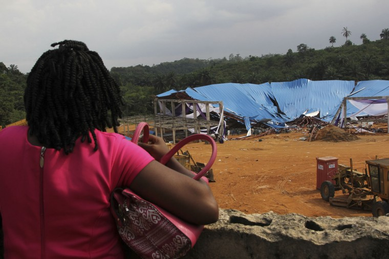 A woman stands to look at the site of a collapsed church in Uyo, Nigeria, Sunday, Dec. 11, 2016. Metal girders and the roof of a crowded church collapsed onto worshipers, Saturday, killing at least 160 people with the toll likely to rise, a hospital director said Sunday. (AP Photo)
