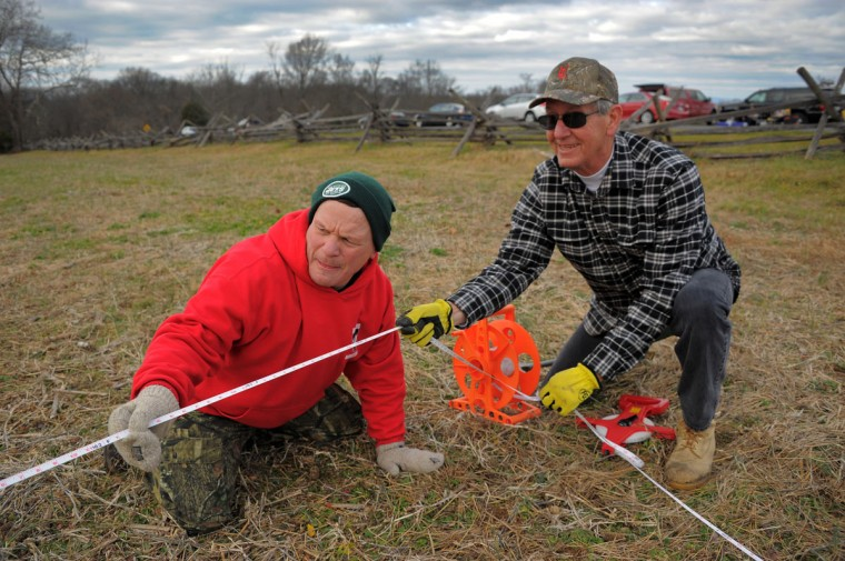 J. LaWald and Mike Colie of Herndon, Va. intersect two measuring tapes to begin placement of luminaries during the 28th Annual Memorial Illumination of over 23,000 luminaries at Antietam National Battlefield. (Karl Merton Ferron/Baltimore Sun)