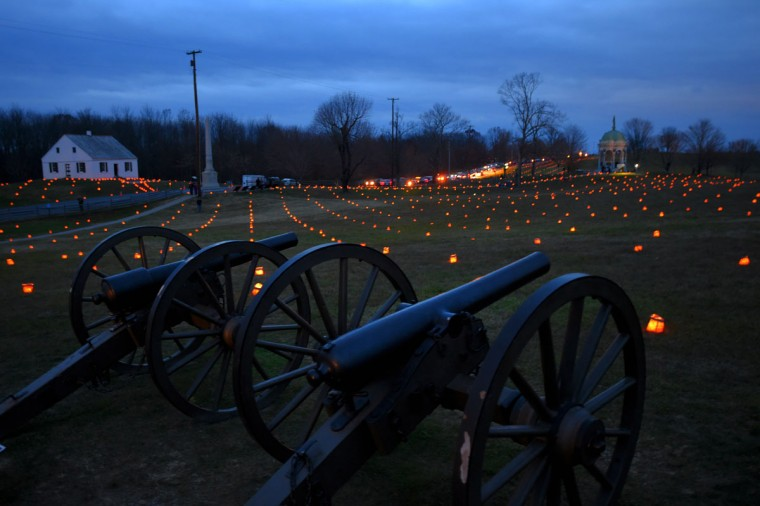 Cannons pointing toward the Maryland Monument (right) rest among hundreds of luminaries while traffic waits on historic Hagerstown Pike to pass the Dunker Church (left) during the 28th Annual Memorial Illumination of over 23,000 luminaries at Antietam National Battlefield. (Karl Merton Ferron/Baltimore Sun)