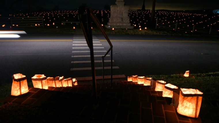 The Ohio 5th, 7th, and 66th Infantry Monument rests near a crosswalk on historic Hagerstown Pike in front of the illuminated steps leading to the Dunker Church during the 28th Annual Memorial Illumination of over 23,000 luminaries at Antietam National Battlefield. (Karl Merton Ferron/Baltimore Sun)