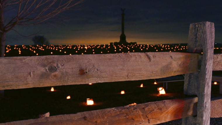 The sun sets behind the New York Monument while luminaries glow in the surrounding field during the 28th Annual Memorial Illumination of over 23,000 luminaries at Antietam National Battlefield. (Karl Merton Ferron/Baltimore Sun)