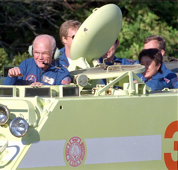 Then-Sen. John Glenn controls a small armored personnel carrier during training, on Wednesday, Oct. 7, 1998. Fire training officer Capt. George Hoggard, left front, trained the seven-member crew how to drive the M1-113 carrier. (Red Huber/Orlando Sentinel/TNS)