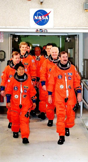 Discovery crew members file out of the Operations and Checkout Building at Kennedy Space Center on Friday, Oct. 9, 1998. They are Chiaki Mukai, front left, clockwise, pilot Steve Lindsey, Scott Parazynski, Stephen Robinson, Pedro Duque, Sen. John Glenn and commander Curt Brown. (Red Huber/Orlando Sentinel/TNS)