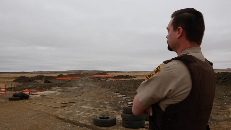 Jon Moll, Sheriff's Deputy with the Morton County Police Department, looks out at a completed portion of the Dakota Access oil pipeline. For months, Moll has been responding to the Standing Rock protests against the pipeline. (Zoeann Murphy, The Washington Post)