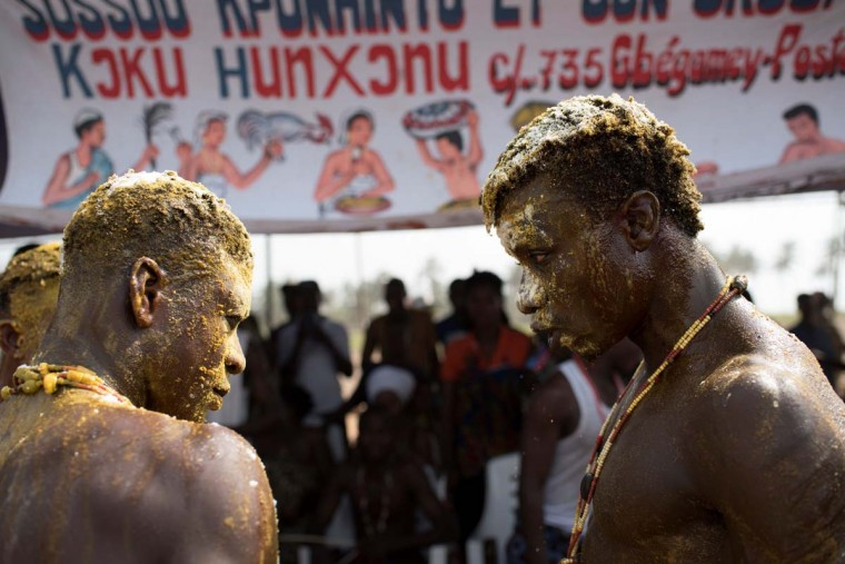 Voodoo devotees covered in oil, powder and yellow colorant talk to each other at the annual Voodoo Festival on January 10, 2017 in Ouidah. (STEFAN HEUNIS/AFP/Getty Images)