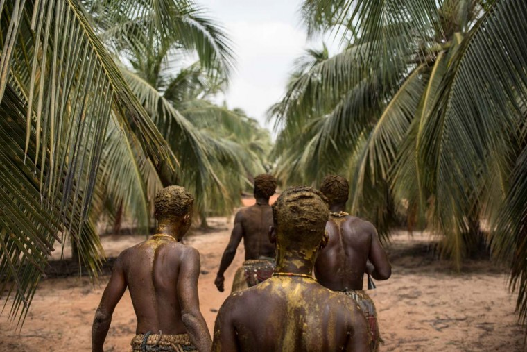 Voodoo devotees walk through a palm tree plantation on their way to the annual Voodoo Festival on January 10, 2017 in Ouidah. (STEFAN HEUNIS/AFP/Getty Images)