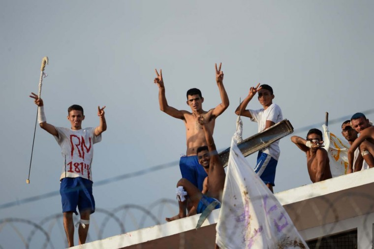 Inmates wave from the prison roof at the Alcacuz Penitentiary Center during a riot in Rio Grande do Norte, Brazil on January 18, 2017. Brazil's government on January 17 ordered the armed forces to help secure the country's overcrowded jails as police fought to separate rival gangs of inmates in one prison following a massacre. (ANDRESSA ANHOLETE/AFP/Getty Images)