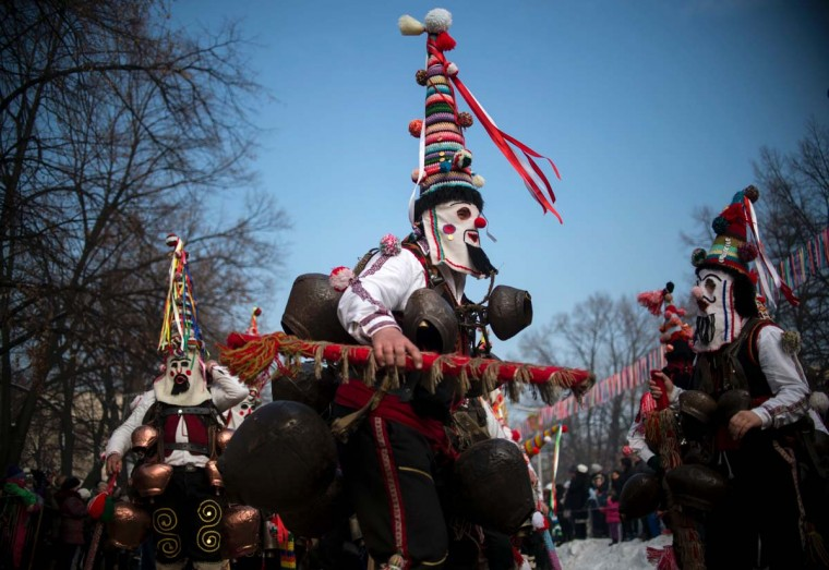 "Dancers, known as ""Kukeri"", perform on January 29, 2017 during the International Festival of the Masquerade Games in Pernik, near the capital Sofia. The three-day festival, which started on January 27, has participants sporting multi-colored masks, covered with beads, ribbons and woolen tassels while the main dancer, ladened with bells to drive away sickness and evil spirits, sways like a wheat spikelet heavy with grain. (NIKOLAY DOYCHINOV/AFP/Getty Images)"