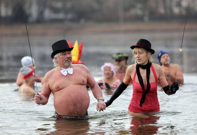 "Swimmers of the association ""Berliner Seehunde"" (Berlin Seals) pose for a picture during the traditional New Year's swimming event on January 1, 2017 in the cold water of lake Orankesee in Berlin. (AFP PHOTO / dpa / Jorg Carstensen)"