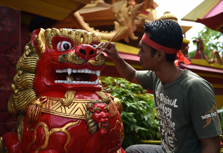 "A worker paints a statue at a Chinese temple ahead of the Lunar New Year festival in Denpasar, on Indonesia's Bali island on January 23, 2017. Indonesian-Chinese are preparing to celebrate the Lunar New Year or ""Spring Festival, which falls on January 28 this year, for the start of the Year of the Rooster. (Sonny Tumbelaka/AFP/Getty Images)"
