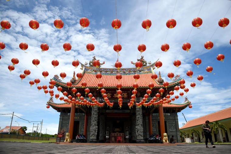 "A man walks by a Chinese temple decorated with lanterns ahead of the Lunar New Year festival in Denpasar, on Indonesia's Bali island on January 23, 2017. Indonesian-Chinese are preparing to celebrate the Lunar New Year or ""Spring Festival, which falls on January 28 this year, for the start of the Year of the Rooster. (Sonny Tumbelaka/AFP/Getty Images)"