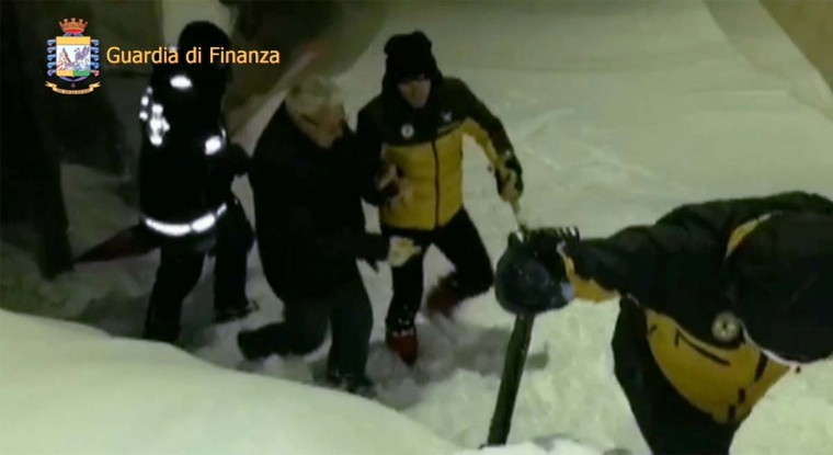 This image grab made from a video handout released by the Guardia di Finanza on January 19, 2017 shows a man being escorted by Alpine policemen (right) and a fireman (left) outside the Hotel Rigopiano, near the village of Farinfola, on the eastern lower slopes of the Gran Sasso mountain. Up to 30 people were feared to have died after an Italian mountain Hotel Rigopiano was engulfed by a powerful avalanche in the earthquake-ravaged center of the country. Italy's Civil Protection agency confirmed the Hotel Rigopiano had been engulfed by a (six-feet) high wall of snow and that emergency services were struggling to get ambulances and diggers to the site. (AFP PHOTO / Guardia di Finanza press office / Handout)