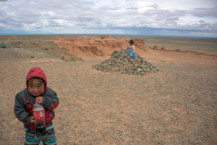 This picture taken on June 27, 2016 shows a girl with a bottle standing on top of the Flaming Cliffs in the Gobi desert. For years, herder Gelegrash had a sideline bringing tourists to see a dinosaur skull hidden near the Flaming Cliffs in Mongolia's Gobi desert. Then, one day, it was gone. It is one of thousands of ancient fossils that have disappeared from the country since American explorer Roy Chapman Andrews -- supposedly the inspiration for the movie character Indiana Jones -- discovered dinosaur eggs there nearly a century ago. (JOHANNES EISELE/AFP/Getty Images)