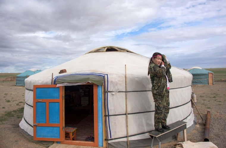 This picture taken on June 27, 2016 shows national park ranger Surenjav Munkhsaikhan trying to get signal for her mobile phone next to a yurt near the Flaming Cliffs in the Gobi desert. For years, herder Gelegrash had a sideline bringing tourists to see a dinosaur skull hidden near the Flaming Cliffs in Mongolia's Gobi desert. Then, one day, it was gone. It is one of thousands of ancient fossils that have disappeared from the country since American explorer Roy Chapman Andrews -- supposedly the inspiration for the movie character Indiana Jones -- discovered dinosaur eggs there nearly a century ago. (JOHANNES EISELE/AFP/Getty Images)