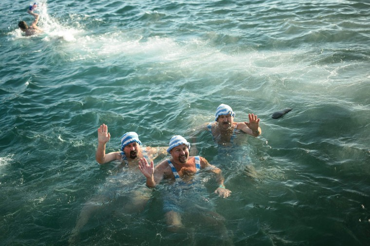 Men wave from the water during a traditional New Year's swim in the Adriatic sea in Portoroz, Slovenia, on January 1, 2017. (AFP PHOTO / Jure MAKOVEC)