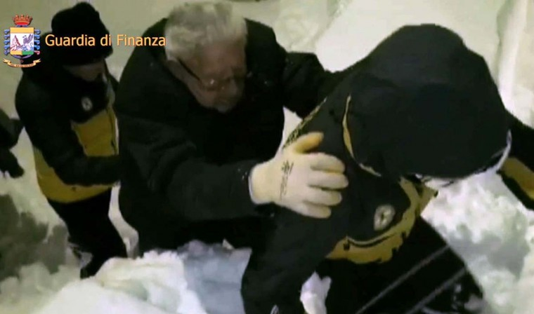 This image grab made from a video handout released by the Guardia di Finanza on January 19, 2017 shows a man being escorted by Alpine policemen (right) outside the Hotel Rigopiano, near the village of Farindola, on the eastern lower slopes of the Gran Sasso mountain. Up to 30 people were feared to have died after an Italian mountain Hotel Rigopiano was engulfed by a powerful avalanche in the earthquake-ravaged center of the country. Italy's Civil Protection agency confirmed the Hotel Rigopiano had been engulfed by a (six-feet) high wall of snow and that emergency services were struggling to get ambulances and diggers to the site. (AFP PHOTO / Guardia di Finanza press office / Handout)