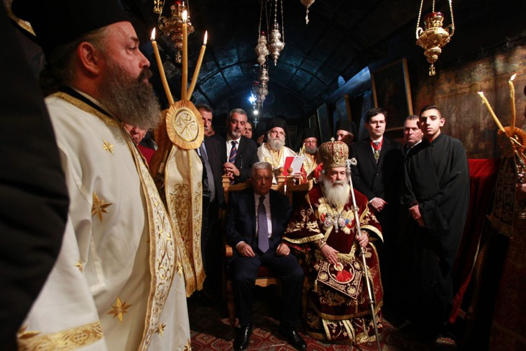 Palestinian President Mahmoud Abbas (L) attends the Christmas Midnight Mass for the Greek Orthodox as Greek Orthodox Patriarch of Jerusalem Theophilos III (R) leads the midnight mass at the Church of the Nativity in the biblical West Bank town of Bethlehem as Orthodox Christmas celebrations kicked off on January 7, 2017, in the traditional birthplace of Jesus Christ. (AFP PHOTO / MUSA AL SHAER)