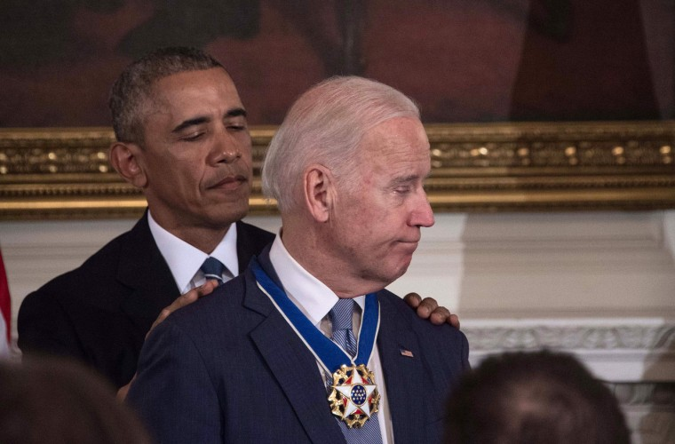 U.S. President Barack Obama pats Vice President Joe Biden on the shoulders after he awarded him the Presidential Medal of Freedom during a tribute to Biden at the White House in Washington, DC, on January 12, 2017. (Nicholas Kamm/AFP/Getty Images)