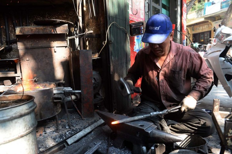 This picture taken on December 8, 2016 shows Nguyen Phuong Hung working at his shop on Lo Ren street in downtown Hanoi. Sitting before a bright orange flame, Vietnamese blacksmith Nguyen Phuong Hung prods a fire pit with a long metal rod before he hammers, bends, and contorts glowing steel into a giant drill bit. Hung, who toils away in his tiny corner stall in downtown Hanoi, is the last remaining blacksmith on Hanoi's Lo Ren street, named after the masters of metal it was once known for. (HOANG DINH NAM/AFP/Getty Images)