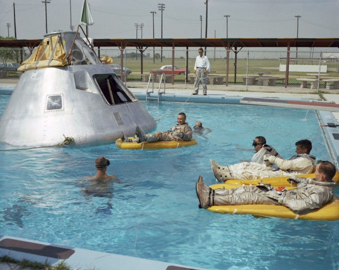 In this June 1966 photo made available by NASA, the Apollo 1 crew practices water evacuation procedures with a full scale model of the spacecraft at Ellington AFB, near the then-Manned Spacecraft Center, Houston. In the rafts at right are astronauts Ed White and Roger Chaffee, foreground. In a raft near the spacecraft is astronaut Virgil Grissom. (NASA via AP)