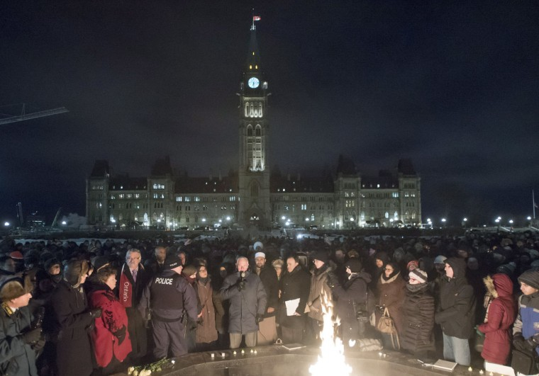 People surround the Centennial Flame as Canada's Governor General David Johnston speaks in response to Sunday's deadly shooting at a Quebec City mosque, during a vigil on Parliament Hill in Ottawa, Ontario, Monday, Jan. 30, 2017. (Justin Tang/The Canadian Press via AP)