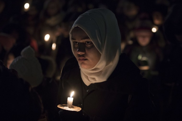 A woman joins others as they gather to observe a candlelight vigil in Toronto on Monday, Jan. 30, 2017, for victims of Sunday's deadly shooting at a Quebec City mosque. (Chris Young/The Canadian Press via AP)