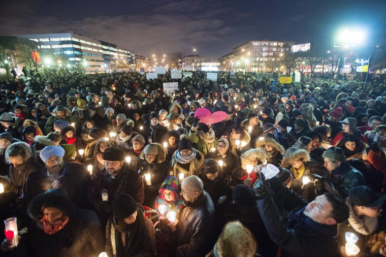 People hold candles for victims of Sunday's deadly shooting at a Quebec City mosque, during a vigil in Montreal on Monday, Jan. 30, 2017. Alexandre Bissonnette, a French Canadian suspect known for his far-right, nationalist views, was charged Monday with six counts of first-degree murder and five counts of attempted murder in the shooting rampage at a Quebec City mosque that Canada's prime minister called an act of terrorism again Muslims. (Ryan Remiorz/The Canadian Press via AP)
