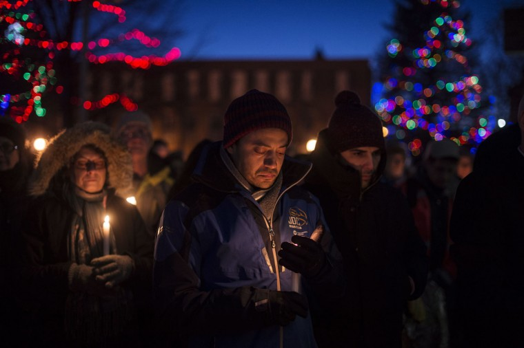 People hold a moment of silence during a vigil in Moncton, New Brunswick, Monday, Jan. 30, 2017, for victims of Sunday's shooting at a Quebec City mosque. (Darren Calabrese/The Canadian Press via AP)