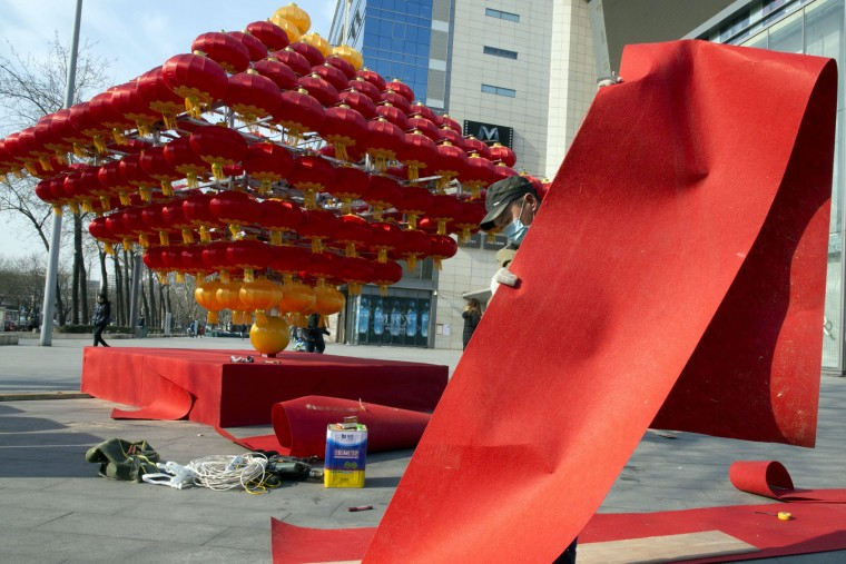 A worker prepares Chinese New Year decorations outside a mall in Beijing Monday, Jan. 23, 2017. Chinese worldwide celebrates the Lunar New Year on Jan. 28 with family reunions, fire crackers and traditional food. (AP Photo/Ng Han Guan)