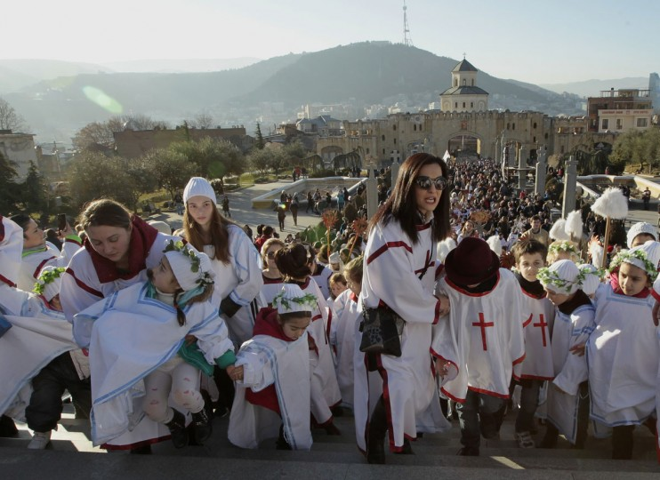 Georgians take a part in a religious procession to mark Orthodox Christmas in Tbilisi, Georgia, Saturday, Jan. 7, 2017. Christmas falls on Jan. 7 for Orthodox Christians that use the old Julian calendar instead of the 16th-century Gregorian calendar adopted by Catholics and Protestants and commonly used in secular life around the world. (AP Photo/Shakh Aivazov)