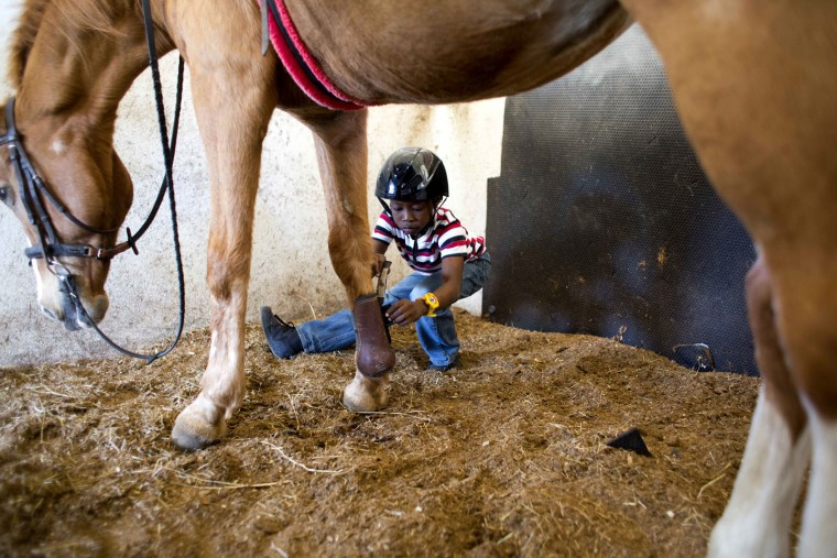In this Jan. 7, 2017 photo, Judeley Hans Debel squats down to remove a boot from Tic Tac, holding out his prosthetic leg after his therapeutic riding lesson at the Chateaublond Equestrian Center in Petion-Ville, Haiti. Anne-Rose Schoen, who founded the equestrian center, said perhaps the most important thing about therapeutic riding is it makes youngsters happy in a country where disabled people face enormous challenges. (AP Photo/Dieu Nalio Chery)